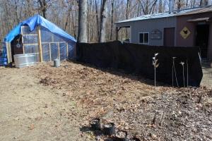 Black tarp drying on fence